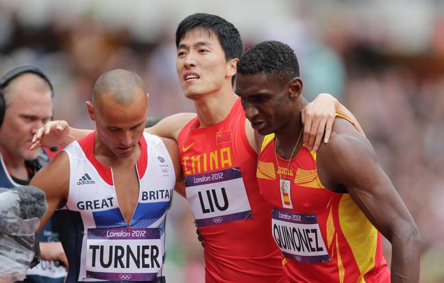 Xiang Liu was escorted from the track by his rival competitors. Credit: PA
