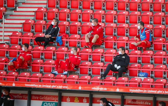 Substitutes and coaches social distancing during the game. Image: PA Images