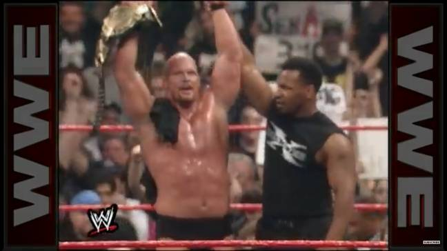 Mike Tyson raises Stone Cold Steve Austin's arm aloft after helping him to victory. Image: WWE.com