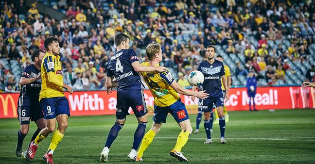 Matt Simon holds the ball up against Melbourne Victory. Credit: Twitter/Central Coast Mariners