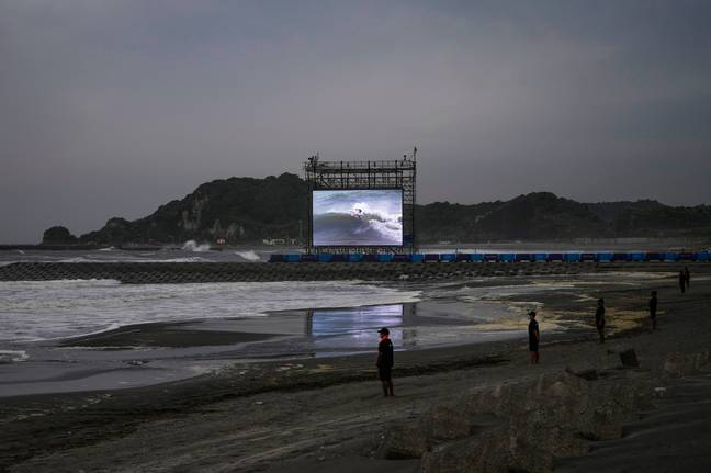 A giant screen displays the third round of men's surfing competition at the 2020 Summer Olympics, Monday, July 26, 2021, at Tsurigasaki beach in Ichinomiya, Japan. (Credit: PA)