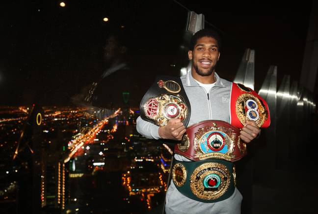 Joshua shows off the belts he won back. Image: PA Images