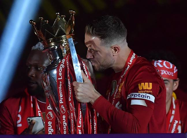 Henderson kisses the Premier League trophy before lifting it. Image: PA Images