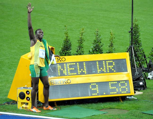 Bolt poses next to the screen showing his world record time. Credit: PA
