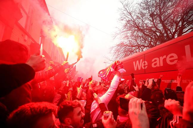 Liverpool fans let off flares. Image: PA