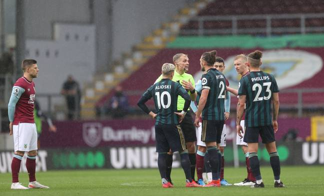 The referee speaks to Alioski and captain Luke Ayling during the game. Image: PA Images