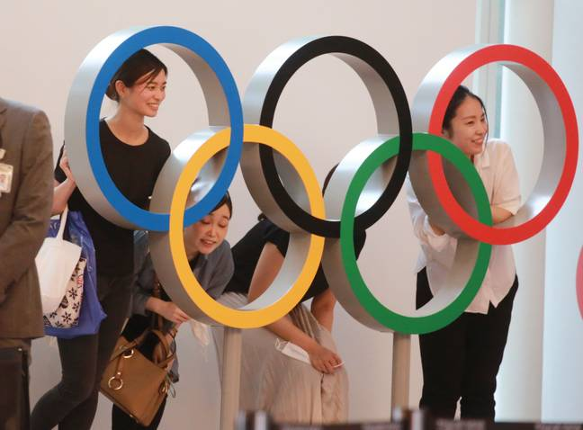Spectators pose for photo with the Olympics Rings display at Haneda International Airport in Tokyo (Credit: PA)