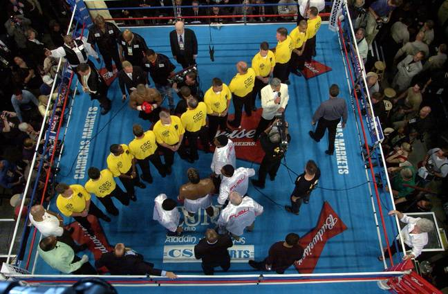 A line of security separates Tyson and Lewis in the ring before their heavyweight championship fight. Image: PA