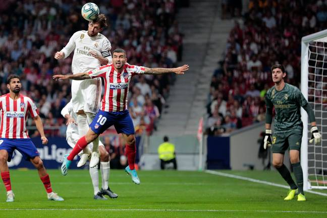 Ramos leaps for the ball in the Madrid derby. Image: PA Images