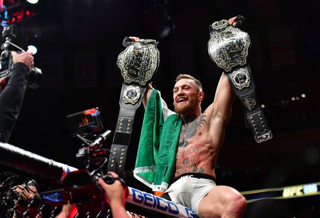 Conor McGregor with his two titles. Image: PA Images