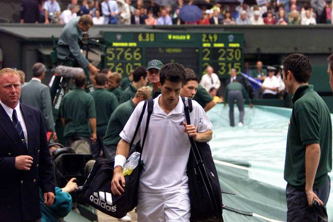 Henman walks off for the rain delay that changed the match. Image: PA Images